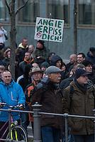"""Etwa 2.000 rechtsradikale Menschen demonstrierten am Samstag den 12. Maerz 2016 in Berlin unter dem Motto """"Merkel muss weg!"""" gegen Angela Merkel, gegen Fluechtlinge und fuer """"Das deutsche Vaterland"""".<br /> Bis auf wenige Ausnahmen waren angereisten Teilnehmer Neonazis und Hooligans, NPD-, Pediga- und AfD-Mitglieder.<br /> Aufgerufen zu dem Aufmarsch hatten die Hooligan-Gruppen """"Buendnis fuer Deutschland"""" und """"Buendnis fuer Berlin"""".<br /> Im Bild: Es wird ein Schild mit der Aufschrift """"Angie verpiss dich!"""" hochgehalten.<br /> 12.3.2016, Berlin<br /> Copyright: Christian-Ditsch.de<br /> [Inhaltsveraendernde Manipulation des Fotos nur nach ausdruecklicher Genehmigung des Fotografen. Vereinbarungen ueber Abtretung von Persoenlichkeitsrechten/Model Release der abgebildeten Person/Personen liegen nicht vor. NO MODEL RELEASE! Nur fuer Redaktionelle Zwecke. Don't publish without copyright Christian-Ditsch.de, Veroeffentlichung nur mit Fotografennennung, sowie gegen Honorar, MwSt. und Beleg. Konto: I N G - D i B a, IBAN DE58500105175400192269, BIC INGDDEFFXXX, Kontakt: post@christian-ditsch.de<br /> Bei der Bearbeitung der Dateiinformationen darf die Urheberkennzeichnung in den EXIF- und  IPTC-Daten nicht entfernt werden, diese sind in digitalen Medien nach §95c UrhG rechtlich geschuetzt. Der Urhebervermerk wird gemaess §13 UrhG verlangt.]"""
