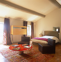 A spacious bedroom with a beamed ceiling and terracotta tiled floor. Modern, contemporary furniture contrasts with the original, rustic features of the room.