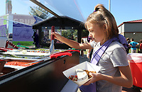 NWA Democrat-Gazette/DAVID GOTTSCHALK Serah (cq) Melancon, a fifth grade student at McNair Middle School, puts fresh garnish on her taco lunch Monday, October 7, 2019, after being served from the Fayetteville Public Schools' Purple Dog Food Truck at the school in Fayetteville. The truck offered an authentic Mexican meal Monday and will visit Holt Middle School on Wednesday.