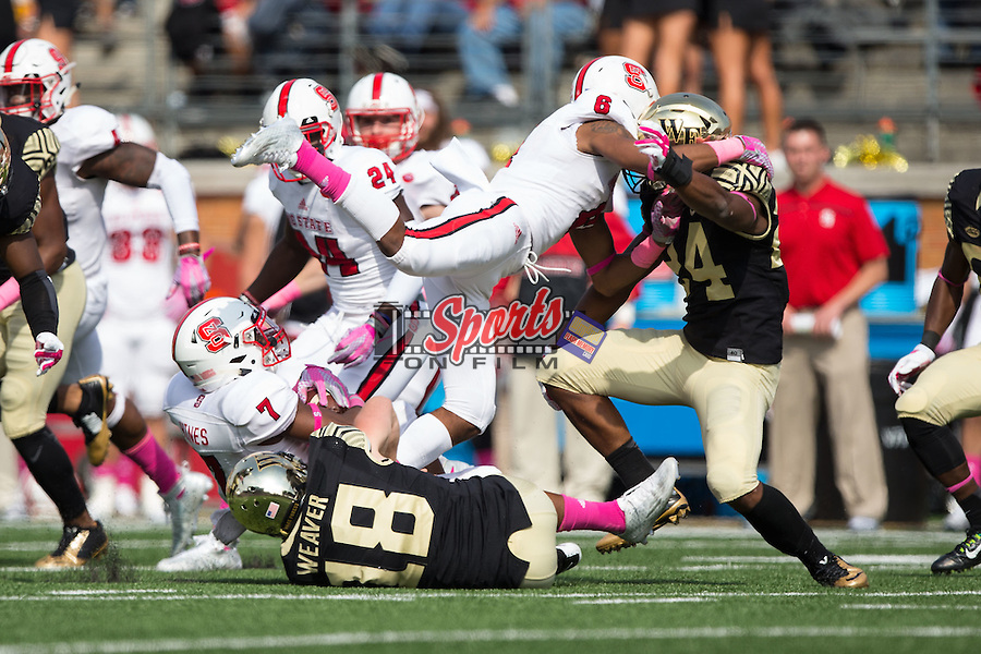 Nyheim Hines (7) of the North Carolina State Wolfpack is tackled by Mike Weaver (18) of the Wake Forest Demon Deacons during first half action at BB&T Field on October 24, 2015 in Winston-Salem, North Carolina.  The Wolfpack defeated the Demon Deacons 35-17.   (Brian Westerholt/Sports On Film)