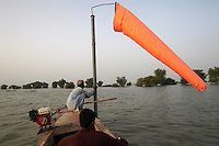 A man holds on to a windsock pole at Dadu airport, which lies completely under water, in Sundh province, Pakistan.