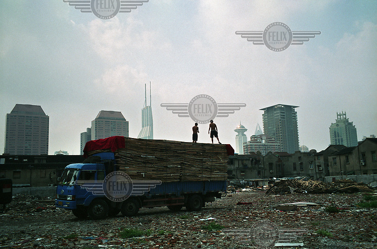 Workers load a truck with scrap wood in a demolished old neighbourhood in Shanghai.
