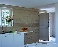 The entrance to the cottage is a stable door that opens directly onto the minimal concrete kitchen