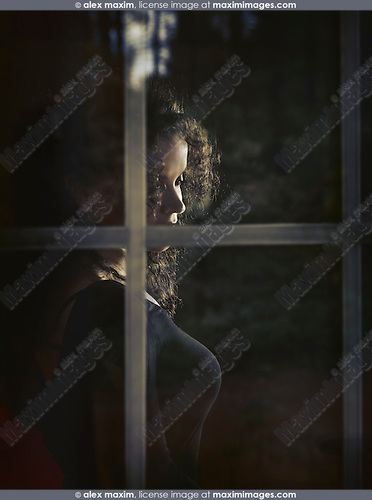 Beautiful woman face behind window glass in dim light
