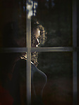 Beautiful woman face behind window glass in dim light