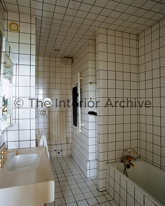 The bathroom is entirely covered in white ceramic tiles with gold fittings for the bath and basin.