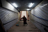 A woman sweeps stairs in an underground shopping area in Kashgar, Xinjiang, China.
