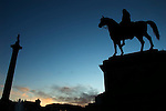 Statue of King George IV on horseback and Nelson's Column in silhouette, Trafalgar Square, London UK