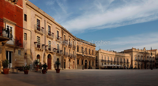 Low angle view of the Piazza del Duomo seen in early morning light in Ortigia, Syracuse, Sicily, pictured on September 14, 2009, in the morning. The 2,700 year old Syracuse is a province and a city in southern Italy on the Island of Sicily. The island Ortigia is the historic centre of Syracuse. Today the city is a UNESCO World Heritage Site. Founded by Ancient Greek Corinthians and allied with Sparta and Corinth, it was a very powerful city-state and one of the major powers of the Mediterranean.  In the 17th century it was heavily destroyed by an earthquake. Many buildings date back to the  19th century when it regained importance. Picture by Manuel Cohen.