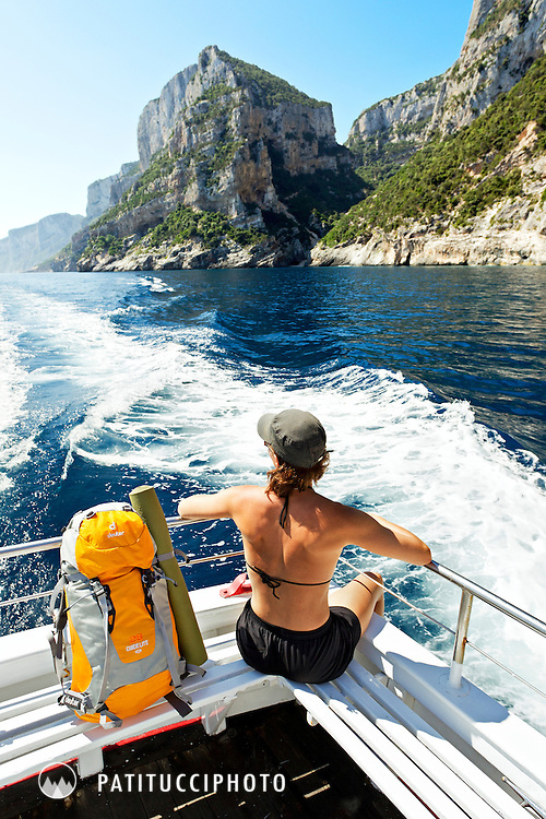A woman on a powerboat shuttle headed for the climbing in Cala Gonone along the shore of the Mediterranean in Sardinia