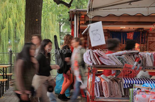 Shoppers at a fabric stall at the Turkish market, held twice weekly on Maybachufer, a street on the Landwehrkanal named after the lawyer and politician Albert von Maybach, Neukolln, Berlin, Germany. Picture by Manuel Cohen