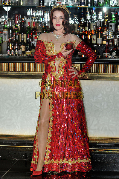 Priscilla Presley.Press launch to star in New Wimbledon Theatre's annual pantomime offering 'Snow White and the Seven Dwarfs' at The Savoy, Strand, London, England..September 26th, 2012.panto costume full length gold red dress crown sequins sequined slit split hand on hip apple  .CAP/BF.©Bob Fidgeon/Capital Pictures.