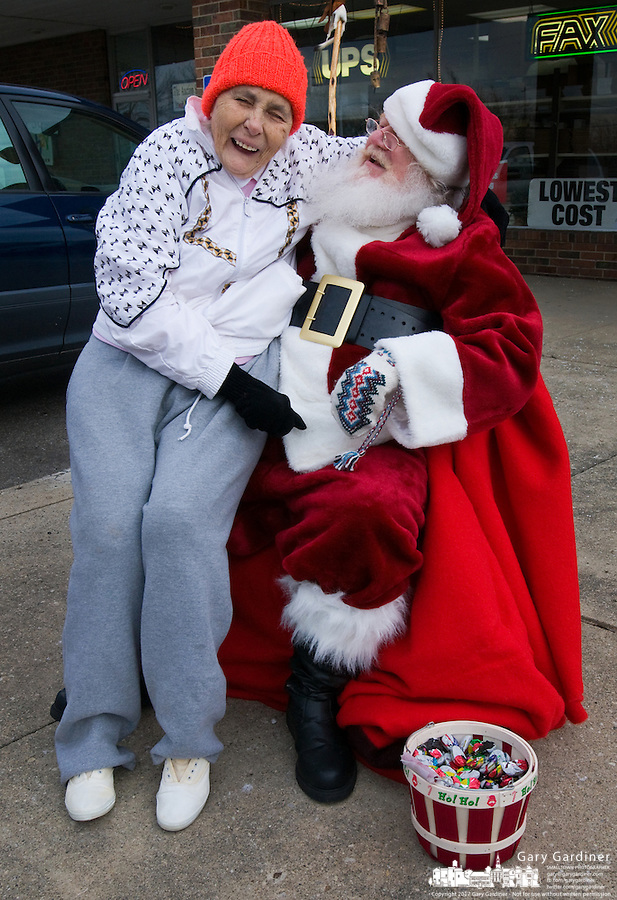 Santa Claus, portrayed by Santa Clarence, a member of the Amalgamated Order of Bearded Santas, poses with an older woman who visited with him outside a shipping store where he greeted young and old to hear their Christmas wishes.
