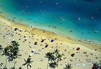 Visitors line the beach at Waikiki while on vacation , island of Oahu