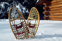 Snowshoes upright in the snow in front of a cabin