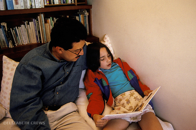Berkeley CA Latino father listening to daughter seven-years-old as she learns to read