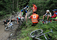 A whole group of riders crash just where Red Cross is treating another man for injuries.  Grenserittet is a 80km mountain bike race starting in the Swedish town of Strömstad, ending up in the Norwegian town Halden. The interest for these kind of bike races has exploded in Norway the last few years, particularly with middle age affluent men.