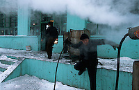 Opera011 20030206 SHANXI, CHINA: A troupe cook rushes to turn off a valve spewing steam at a school, a temporary home for the traveling troupe, in Shanxi Province, China 06 February 2003. The steam is channled to a metal box (background) where buns are made to provide the staple food for the troupe.
