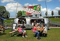 Festival in Amsterdam, De Rollende Keukens.  Rijdende keukens waar bijzondere snacks worden verkocht, zoals koreaanse snacks of vegetarische gyros. Bezoekers van het evenement. Rabarcello