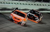 Nov. 16, 2008; Homestead, FL, USA; NASCAR Sprint Cup Series driver Tony Stewart (20) leads teammate Denny Hamlin during the Ford 400 at Homestead Miami Speedway. Mandatory Credit: Mark J. Rebilas-