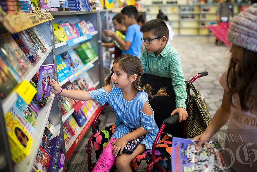 NWA Democrat-Gazette/CHARLIE KAIJO Camila Gonzalez, 8 and Aiden Rodriguez, 8 pick out books on Monday, October 23, 2017 at the Scholastic Book Fair at the Osage Creek Elementary and Creekside Middle School library in Bentonville. The fair continues until Friday, and proceeds go to benefit the schools' library. The library is also collecting donations to buy books for the Benton County Sunshine School's library.