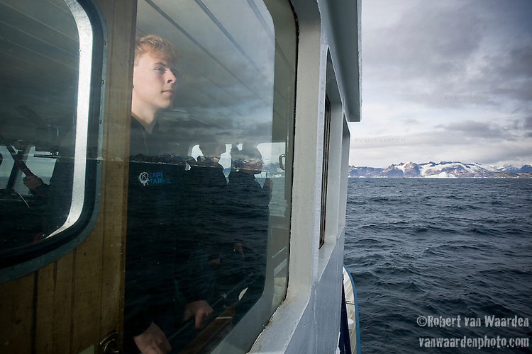 A young teenage man stares out the window at the east Greenland mountains. The man is part of the Cape Farewell Youth Expedition organized by the British Council of Canada. The ship is crossing the ocean from Iceland to Greenland.