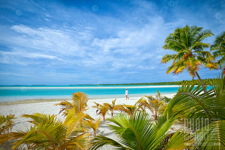 A woman walks on the white sandy beach of One Foot Island, Aitutaki Lagoon, Cook Islands.