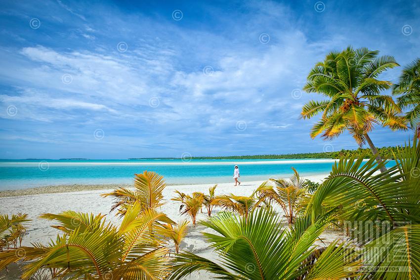 A woman walks on the white sandy beach of One Foot Island, Aitutaki Lagoon, Cook Islands.