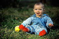 Nine month old baby boy sitting in grass with an apple.