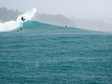 INDONESIA, Mentawai Islands, Kandui Resort,  surfing a wave at Beng Beng in the pouring rain