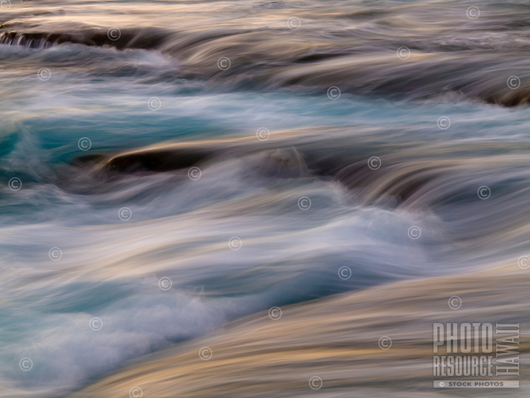 At sunset, a slow camera shutter speed captures the motion of waves surging over the rocky shoreline of Keahole Point, Big Island.
