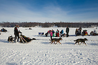 Spectators watch teams including Gerry Willomitzer on Long Lake after leaving the re-start line of the Iditarod sled dog race in Willow, Alaska Sunday, March 3, 2013.