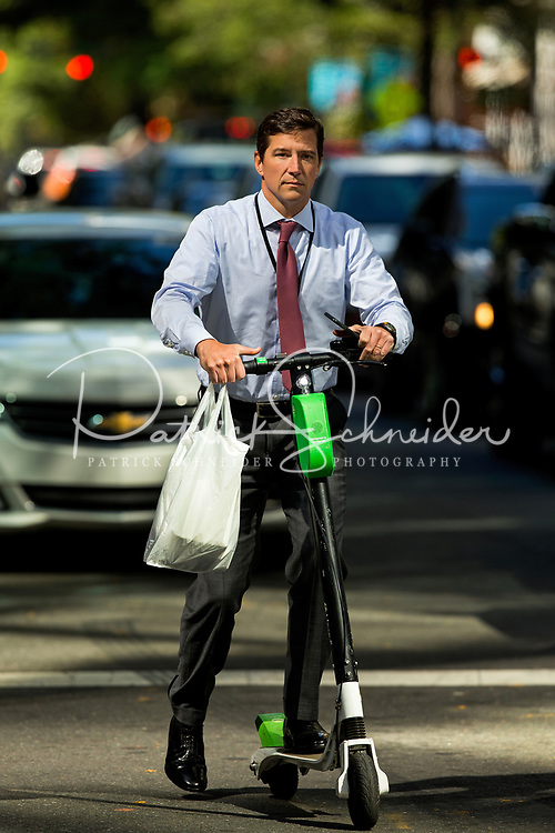 Photography of people riding the Bird and Lime electric scooters in the Uptown/Downtown Charlotte North Carolina area. <br /> Business dressed people riding electric scooters on the downtown Charlotte, North Carolina Streets.<br /> <br /> Charlotte Photographer  PatrickSchneiderPhoto.com