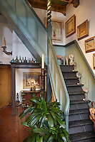 The staircase leading from the open plan living room is lined with Dutch Impressionist paintings including the artist Isaac Israels, while the painting above the colonial chest is by Prague born artist Jaroslav Herbst
