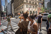 Tourists on Fifth Avenue in New York photograph their newly purchased jewelry with their smartphone on Friday, June 28, 2013. (© Richard B. Levine)