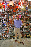 A Turkish vendor stands in front of his stall at the Grand Bizarre selling oil lamps and other metalworks.