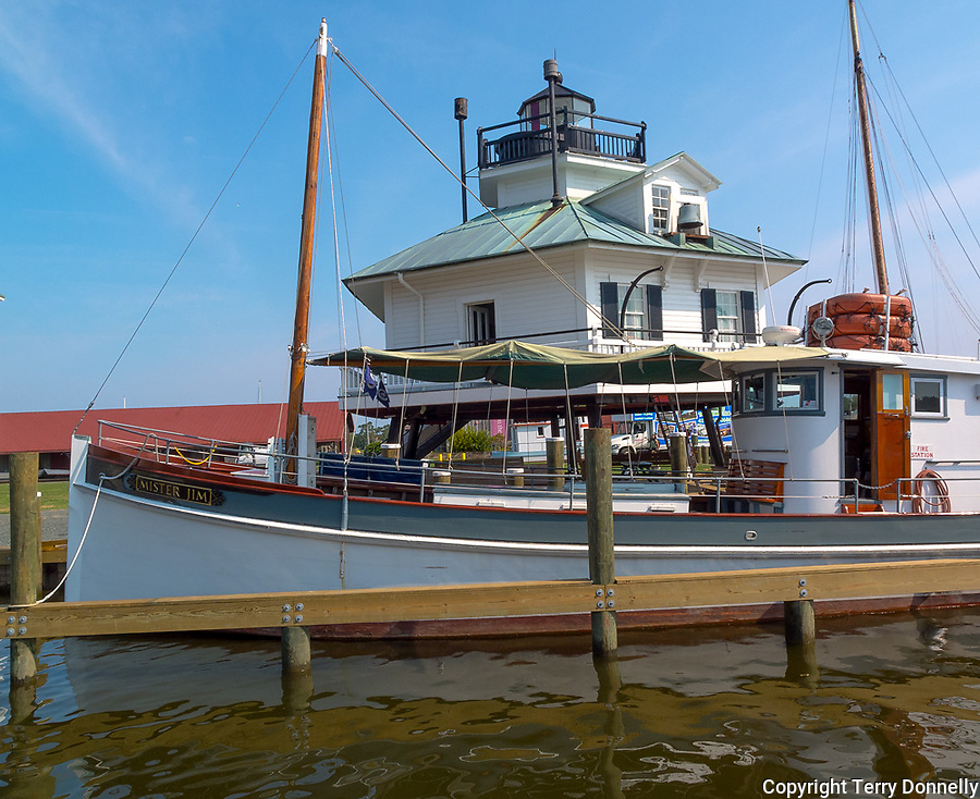 Chesapeake Bay Maritime Museum, St. Michaels, Maryland<br /> Hooper Strait Lighthouse (1879) stands behind the oyster boat Mister Jim on Navy Point