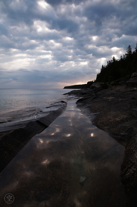 Clouds reflecting on still water at the edge of Little Cove on a stormy morning, Georgian Bay, Ontario