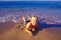 Boy playing in the sand at the ocean's edge
