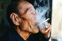 China. Province of Shaanxi. Village Shifeng. Li Hupeng is a young boy. He was kidnapped on may 12 2002, sold to a family in the village of Xiaotan in Henan province. The police found him and brought him back to his family on march 4 2004. Li Hupeng's grandfather smokes a cigarette. © 2004 Didier Ruef