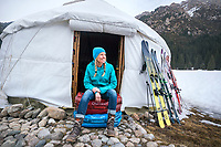 A woman skier arrives at a yurt with duffel bags in the Kyrgyzstan backcountry while on a ski touring trip