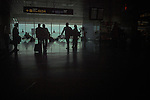 Silhouetted passengers sittting and standing in airport waiting area. Tenerife Sur airport, Tenerife, Spain.