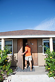 EXUMAS, Bahamas. Yves, Manager of the Fowl Cay Resort entering the resort office.