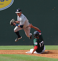 Infielder KC Clabough (5) of the Rome Braves tries to turn a double play but is thwarted by Garin Cecchini (17) of the Greenville Drive on July 8, 2012, at Fluor Field at the West End in Greenville, South Carolina. Clabough was a 28th-round pick of the Atlanta Braves in the 2012 First-Year Player Draft. Greenville won, 12-3. (Tom Priddy/Four Seam Images)