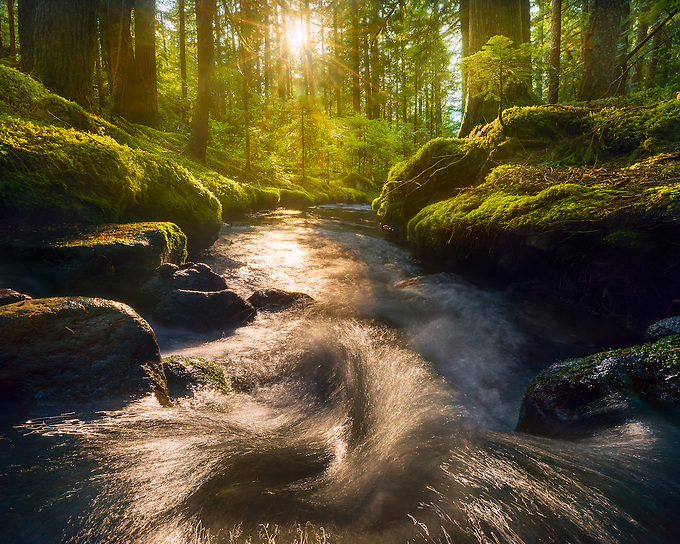 The setting sun illuminates a small cascade in the Mt. Hood wilderness, Oregon. <br />