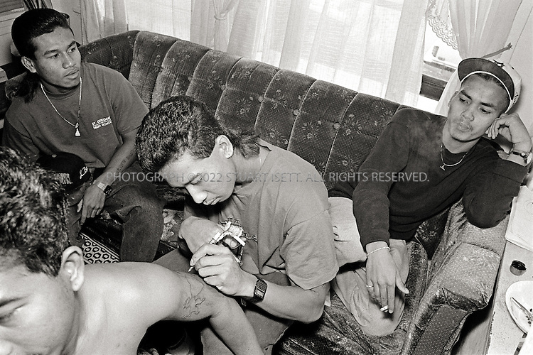 9/1995--Chicago, USA. Using a homemade, 'jail house'  tattoo gun, Gino makes Loco Boyz gang tattoos while Bobby (left) and Tino (right) look on...©2008 Stuart Isett.All rights reservedgg