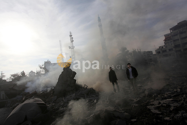 Palestinians look at government offices destroyed in an Israeli airstrike in Gaza City, 21 November 2012. Palestinian militants renewed their rocket fire on Israel 21 November and Israel continued pounding targets in the Gaza Strip, as agreement on a hoped-for truce remained elusive. The Israeli military said it bombed around 100 targets in the Strip overnight, including 50 underground rocket launchers. Photo by Ashraf Amra
