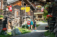 Runners stopped to look at trail signs and their phone navigation app while passing through Zmutt while on the Via Valais, a multi-day trail running tour connecting Verbier with Zermatt, Switzerland.