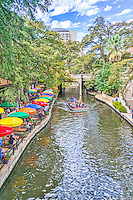 This is another image of the San Antonio river walk with its many colorful umbrellas with a river boat carry toursit to see the sites along the river on this beautiful day with nice blue sky and white puffy clouds.