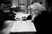 Roma 1996.Un  ospite della Ostello Stazione Termini della caritas  Caritas in Via Marsala  firma il libro per la registrazione della presenza.A guest of the hostel Caritas of Street Marsala.